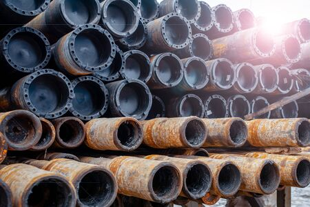 Drill pipe of oil drilling platforms. Stack of oil well casing bundles at the pin end of casing. Downhole drilling rig