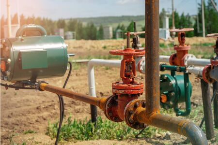 Oil and gas processing plant with pipe line valves. Oil pipeline valves in the oil and gas industry. Valve plug an oil pipeline in the field on a sunny summer day.