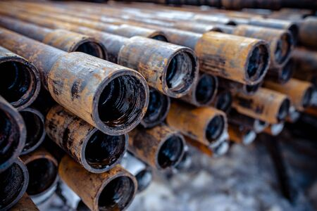Oil Drill pipe. Rusty drill pipes were drilled in the well section. Downhole drilling rig. Laying the pipe on the deck. View of the shell of drill pipes laid in courtyard of the oil and gas warehouse. Standard-Bild - 133610546
