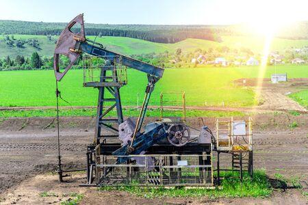 Gelbe Ölpumpen. Pumpenheber. Ausrüstung der Ölindustrie. Rig Energiemaschine für Erdöl Rohöl. Tageslicht, Morgen, blauer Himmel. Nahaufnahme