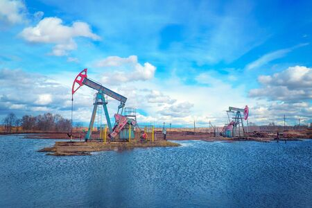 Oil and gas industry. Work of oil pump jack on a oil field. Modern pumpjacks are powered by a prime mover