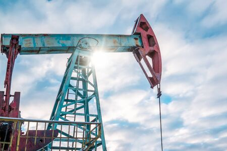 Oil pump jack rocking with pipeline in the background. Rocking machines for power generation. Extraction of oil. A pumpjack is the overground drive for a reciprocating piston pump in an oil well.