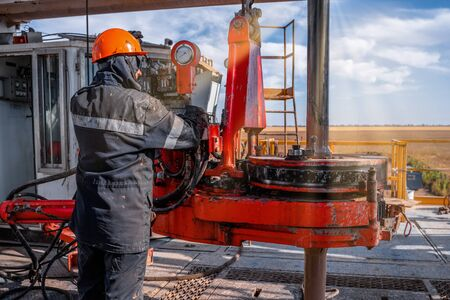 Offshore oil rig worker prepare tool and equipment for perforation oil and gas well at wellhead platform. Making up a drill pipe connection. A view for drill pipe connection from between the stands