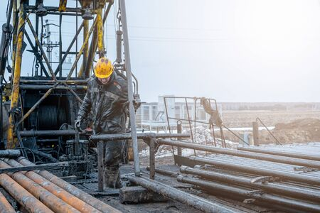 Workover rig working on a previously drilled well trying to restore production through repair. Offshore oil rig worker prepare tool and equipment for perforation oil and gas well at wellhead platform. 写真素材