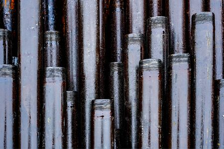 Oil Drill pipe. Rusty drill pipes were drilled in the well section. Downhole drilling rig. Laying the pipe on the deck. View of the shell of drill pipes laid in courtyard of the oil and gas warehouse