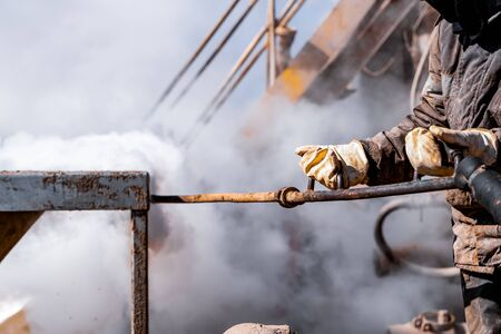 Worker use high pressure steam jet to cleaning splashing the dirt of tube bundle in industrial areas, chemical products or oil and gas plants. Reklamní fotografie