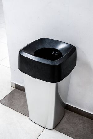 Garbage bin on the floor in a room. Garbage Can in Restroom with Black Bag