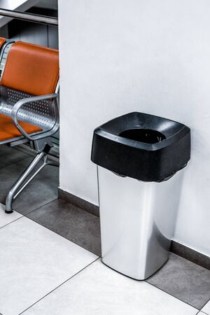 Garbage bin on the floor in a room. Garbage Can in Restroom with Black Bag.