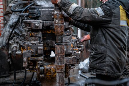 Two working drillers in a uniform, in a helmet and goggles, install drill pipes after lifting them from an oil well after drilling. The concept of a working person.