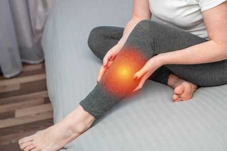 Upset girl looking at camera while sitting on bed and suffering from pain in leg. Tendon knee joint problems on woman leg indicated with red spot. Reklamní fotografie