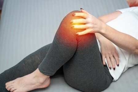 Attractive woman with pain in knee sitting on bed in apartment. Tendon knee joint problems on woman leg indicated with red spot. Banque d'images