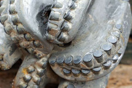 The drill bit, shot close-up with shallow depth of field. Industrial background. Macro shot of drill bits on shelving in stock.