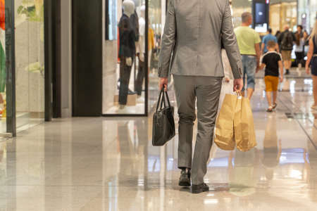Young man shopping in the mall with many shopping bags in his hand