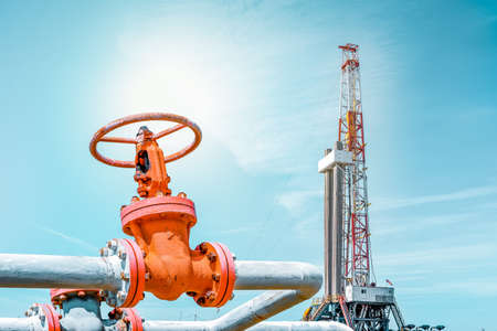 Fountain fittings of a gas well with high-pressure gate valve handwheels. Oil and Gas drilling rig is in the background. Top drive system of drilling rig