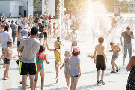 Izhevsk, Russia - July 20, 2020: A children run to console the crying girl among the refreshing splashes of the fountain. Child carefree game in the rays of the rainbow during the summer holidays