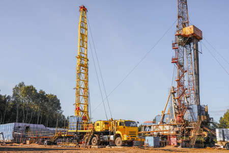 In a row are oil-producing wells. In the background, work is underway to overhaul the well. Drilling rig for drilling oil and gas wells with various equipment and materials. Standard-Bild