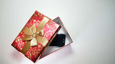Smartphone In Red Gift Box On White Background.