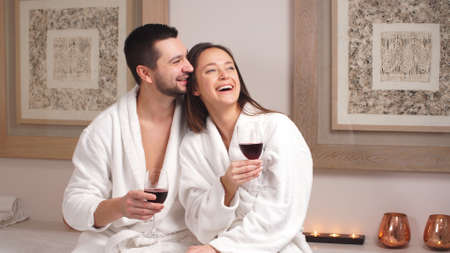 Felice coppia affascinante bere vino e ridere nel moderno salone di benessere. Archivio Fotografico