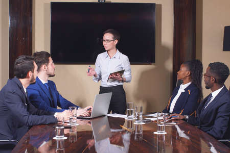 Portrait of female manager addresses a question to colleagues sitting at the table at a business meeting