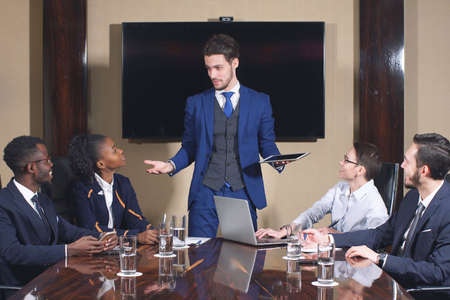 Young attractive businessman makes a presentation of modern product to his colleagues in office interior