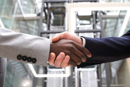 Multiethnic businessmen shaking hands during contract signing at workplace.
