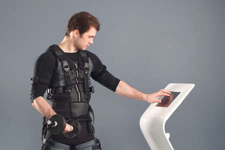 Male athlete pushing on screen on ems machine regulating intensity. Concept of EMS training
