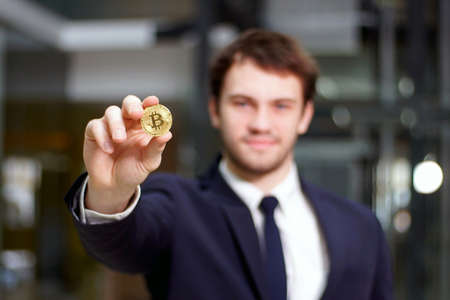 Golden Bitcoin in hand with businessman blurred on background, Digital symbol of new virtual currency.