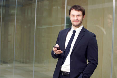 Portrait of businessman. Happy businessman standing in office interior with smartphone in hands, smiling and looking at camera