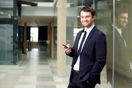 Attractive young businessman uses smartphone in interior of modern office building.