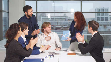Group of businessmen in office congratulate colleague, they clap and smile.