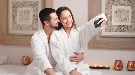 Beautiful young couple makes a selfie in modern wellness salon.