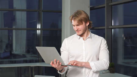 Businessman reading news on laptop computer at coworking space. Male professional making purchases working on laptop in office.