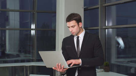 Portrait of confident modern businessman with laptop in hands. Фото со стока