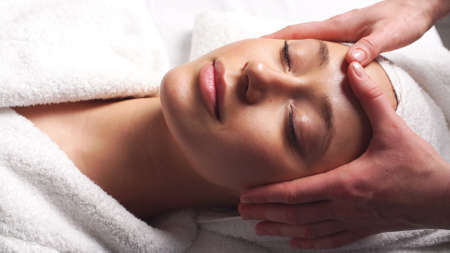 Face Massage in beauty spa salon. Skin care, wellness, beauty treatment.