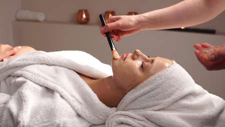 Beautiful woman with facial mask at beauty salon.Applying facial mask at woman face at beauty salon.Spa therapy for young woman receiving facial mask at beauty salon.Beautician does face mask.
