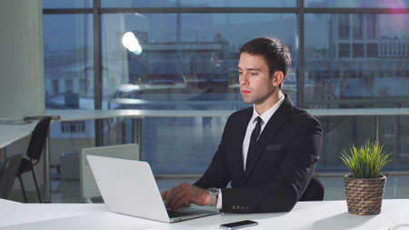 Young modern businessman working at desk in office using laptop.
