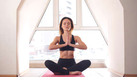 Attractive Young Woman Sitting on Lotus Position on Floor Фото со стока