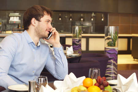 Awesome handsome businessman in restaurant making a phone call, business meeting. Zdjęcie Seryjne