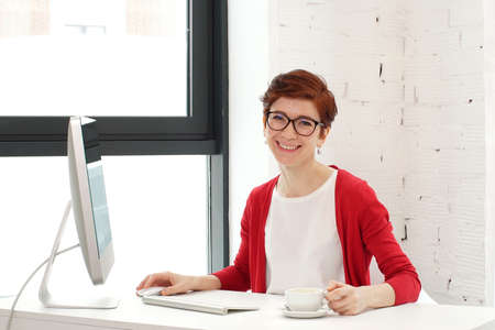 Young woman working in office, sitting at desk, using computer and looking on camera