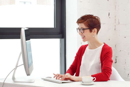 Young woman working in office, sitting at desk, using computer and looking on screen