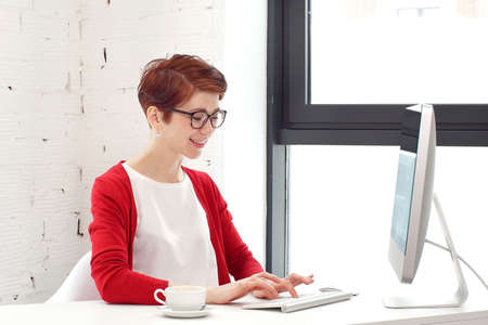 Portrait of businesswoman wearing glasses working on computer and looking at camera in office