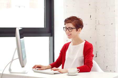 Business woman typing on keyboard in bright office