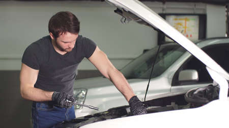 Young Technician Man Making Engine Service of Car in Garage