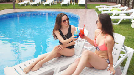 Best girlfriends on vacation, drinking cocktails lying on loungers by the pool. Фото со стока