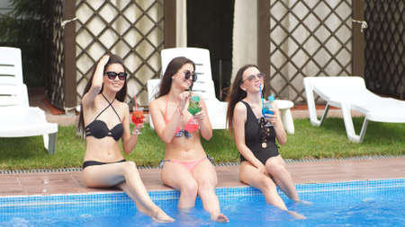 Young attractive girls celebrate their birthday resting by the pool. Girls drink multi-colored alcoholic cocktails lowering their legs into the water. Фото со стока