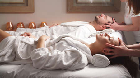 Beautiful couple lying down on massage beds enjoying a head massage in luxury spa. Relaxing and health.