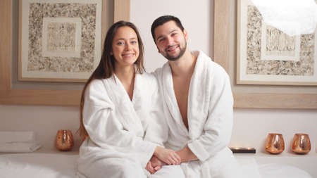 Beautiful pleasant couple having good time in modern wellness salon, lying on massage table, beauty treatment concept