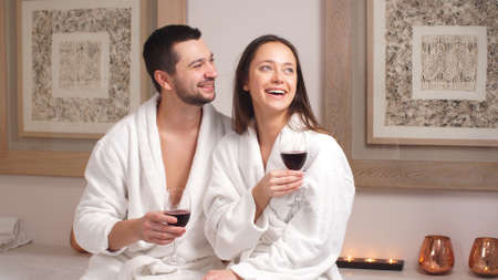 Happy charming couple drinking wine and laughing in modern wellness salon.