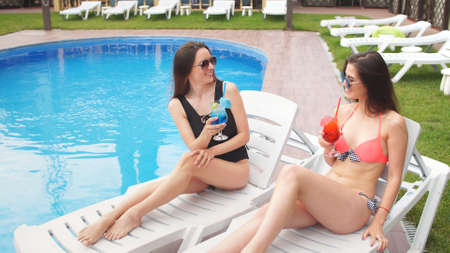 Young charming girls enjoy cocktails resting on the ganders near the pool.