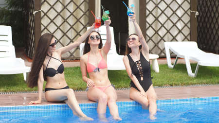 Womans body with cocktail glass near swimming pool.
